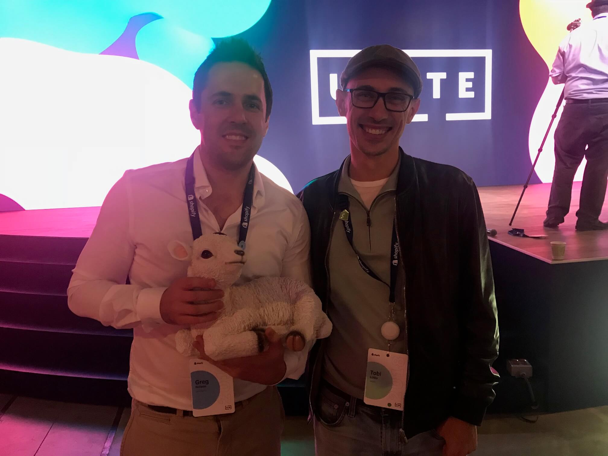 Greg Nelson and Shopify CEO standing with A lamb at Shopify Unite