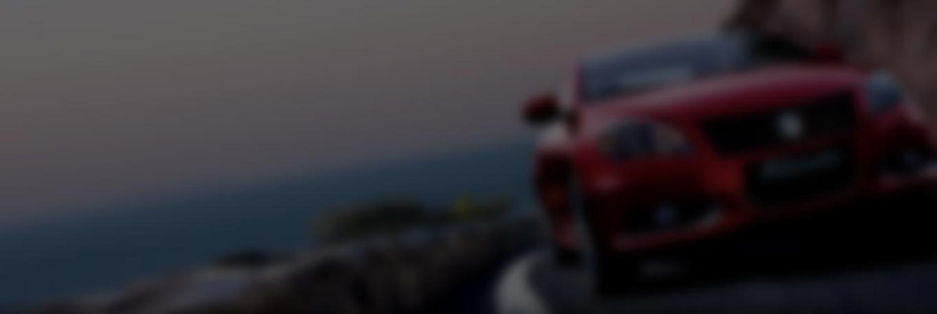Red suzuki driving on winding road